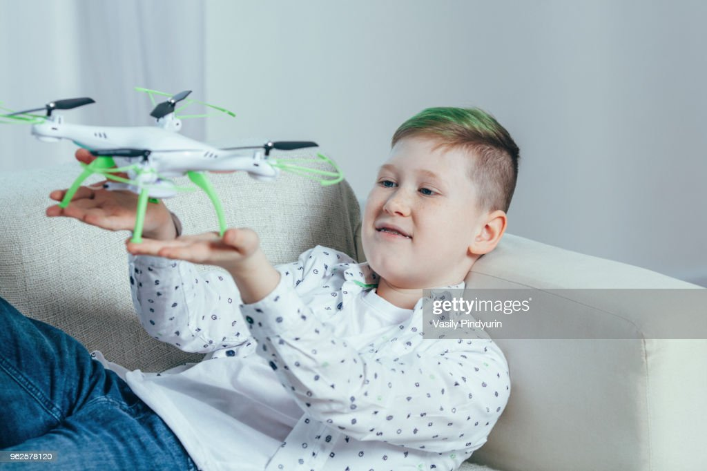 Smiling boy lying on sofa holding drone in living room at home : Stock Photo