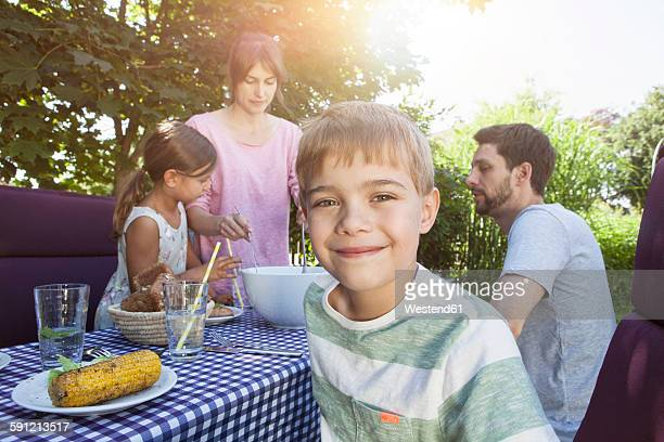Smiling boy on a family barbecue in garden