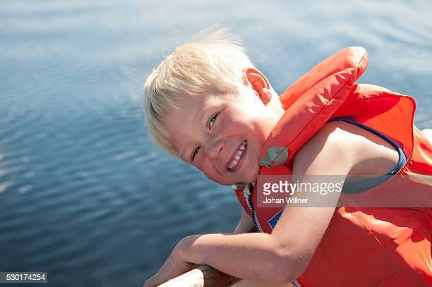 smiling boy on boat - レクサンド ストックフォトと画像