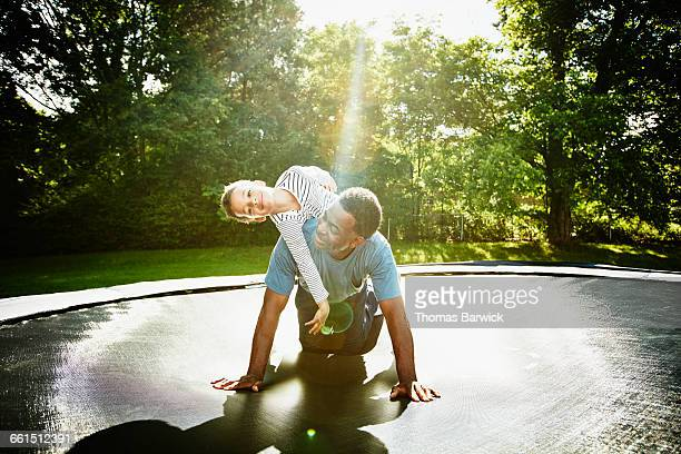 Smiling boy on fathers back while playing