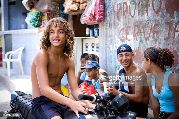 Smiling boy on motorbike with friends.