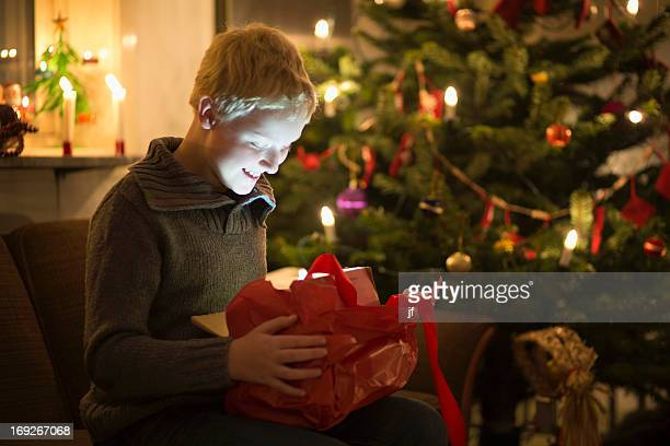 Smiling boy opening Christmas present