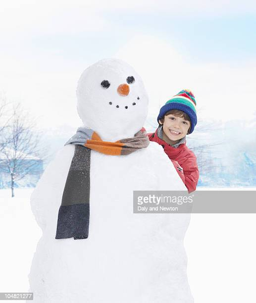 smiling boy peering from behind snowman - snowman stock pictures, royalty-free photos & images