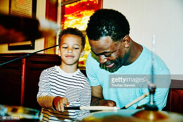 Smiling boy playing drums with father