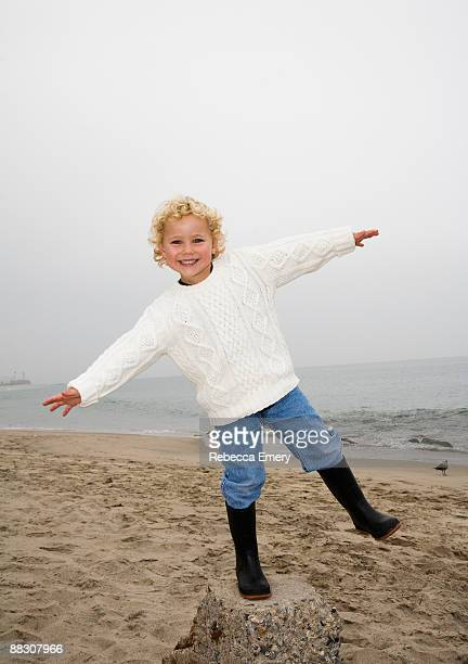 smiling boy playing on beach - emery stock photos and pictures