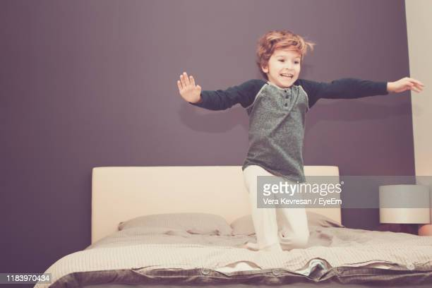 smiling boy playing on bed at home - one boy only stock pictures, royalty-free photos & images