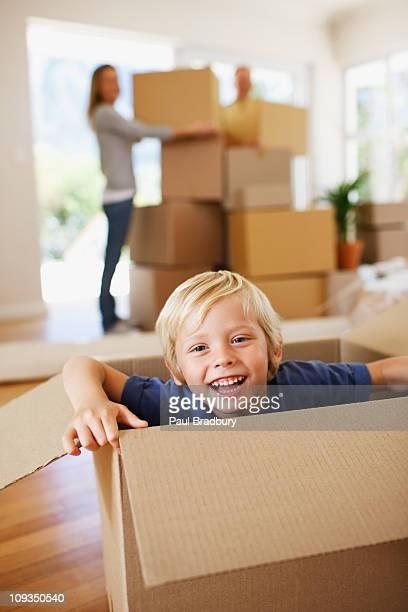Lächelnde Junge spielt auf box in neues Haus