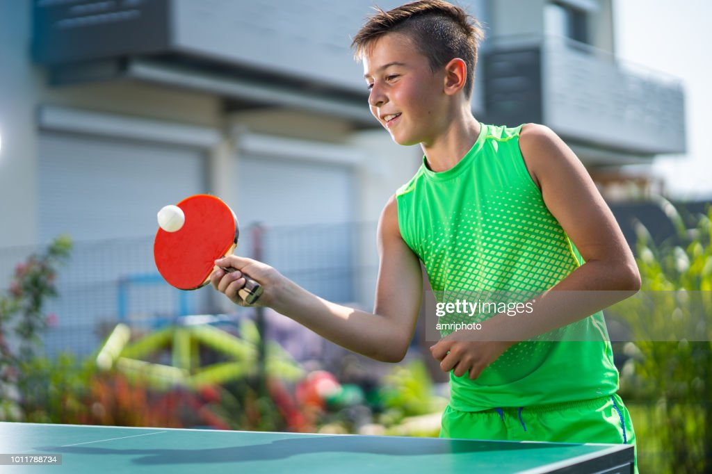 smiling boy playing table tennis in garden : Stock Photo