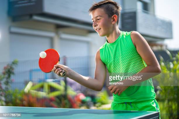smiling boy playing table tennis in garden - table tennis stock pictures, royalty-free photos & images