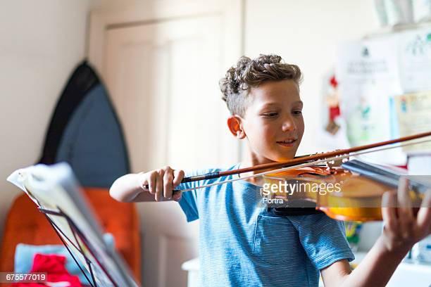 Smiling boy playing violin at home