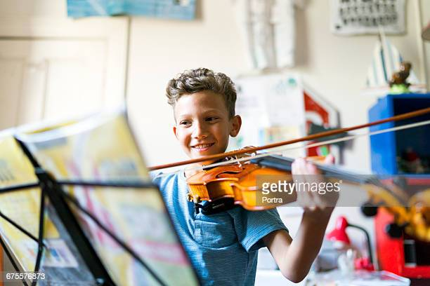 smiling boy playing violin in domestic room - musical instrument stock pictures, royalty-free photos & images