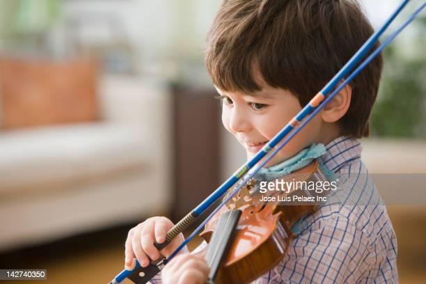 Smiling boy playing violin