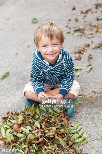 Smiling Boy Playing With Fallen Dry Leaves At Back Yard