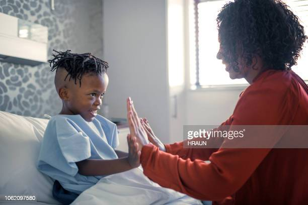 Smiling boy playing with mother in hospital