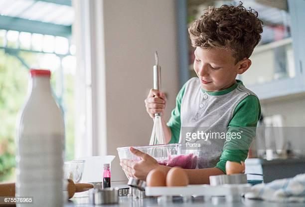 Smiling boy preparing food at kitchen counter