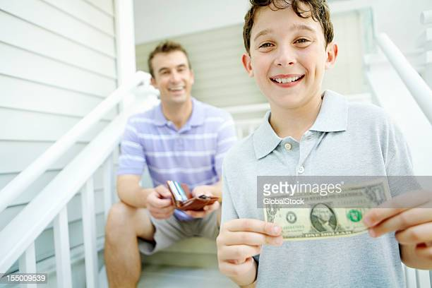 smiling boy receives pocket money from his dad - family dollar stock pictures, royalty-free photos & images