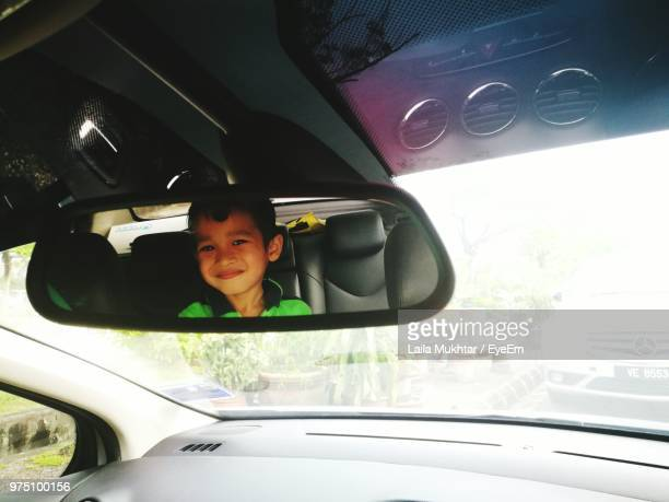 smiling boy reflecting on rear-view mirror of car - vehicle mirror stock photos and pictures