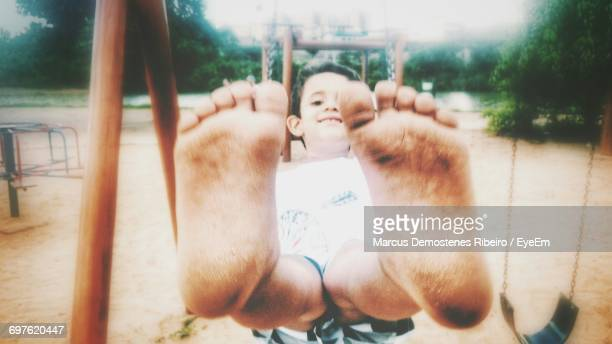 smiling boy showing his messy feet while enjoying swing at park - dirty feet stock pictures, royalty-free photos & images