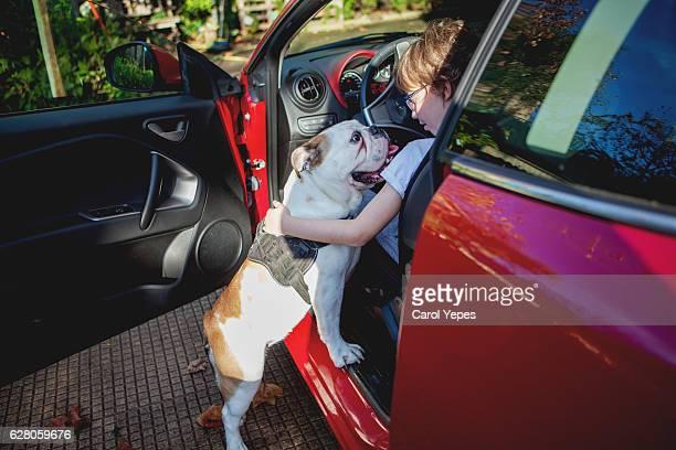 Smiling Boy Sitting In Car With Dog