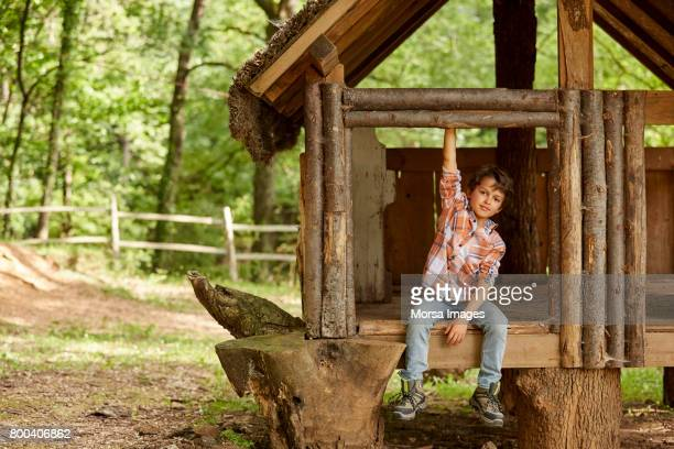 smiling boy sitting in tree house at forest - tree house stock pictures, royalty-free photos & images