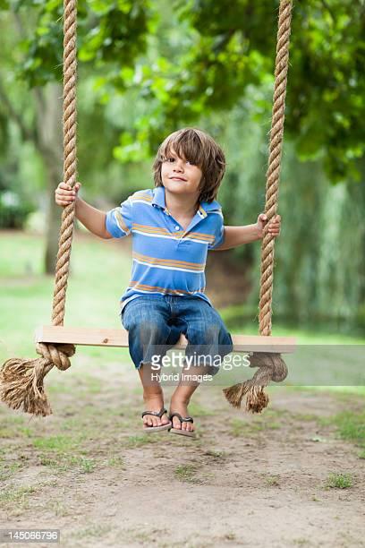 Smiling boy sitting in tree swing