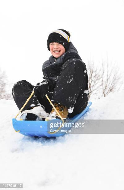 smiling boy sitting on a toboggan on snowy hill on a winter day. - tobogganing stock pictures, royalty-free photos & images