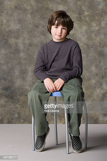 Smiling boy (6-7) sitting on chair, studio shot