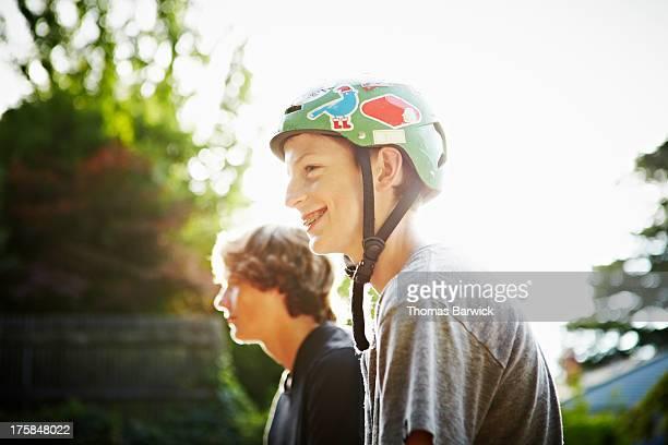 Smiling boy sitting on halfpipe wearing helmet