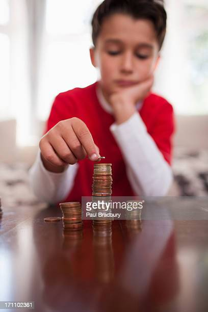 Smiling boy stacking coins