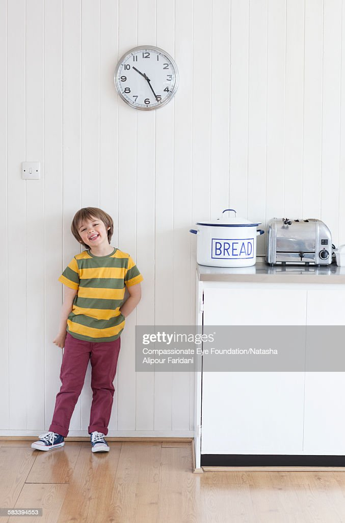 Smiling boy standing in kitchen : Stock Photo