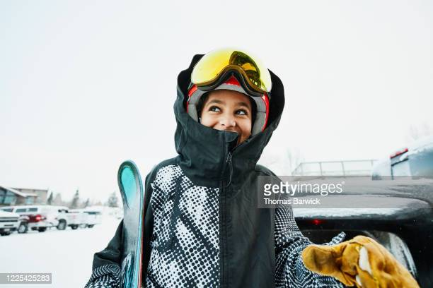 smiling boy standing in parking lot of ski area before going skiing - skiing stock pictures, royalty-free photos & images