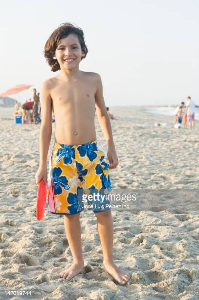 smiling boy standing on beach - zwembroek stockfoto's en -beelden
