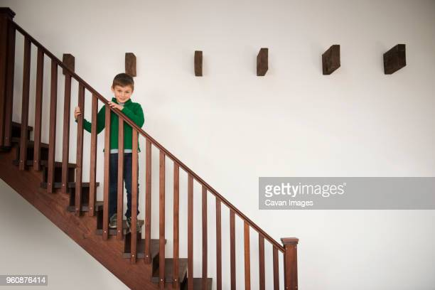 Smiling boy standing on wooden staircase at home