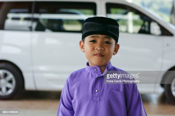 smiling boy standing up in traditional malay attire. - malaysian culture stock pictures, royalty-free photos & images