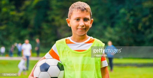 smiling boy standing with football on soccer field - football league stock pictures, royalty-free photos & images