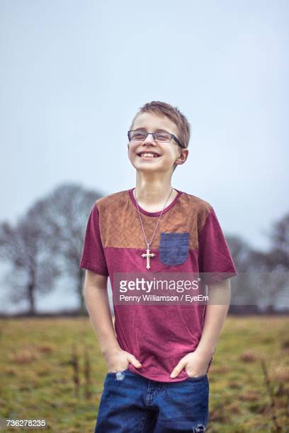 Smiling Boy Standing With Hands In Pockets On Field Against Clear Sky