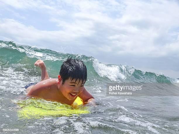 Smiling boy surfing on body board in ocean
