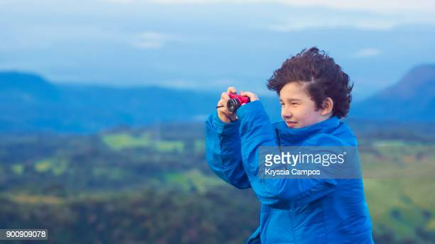 Smiling Boy taking a photo with a point and shoot camera