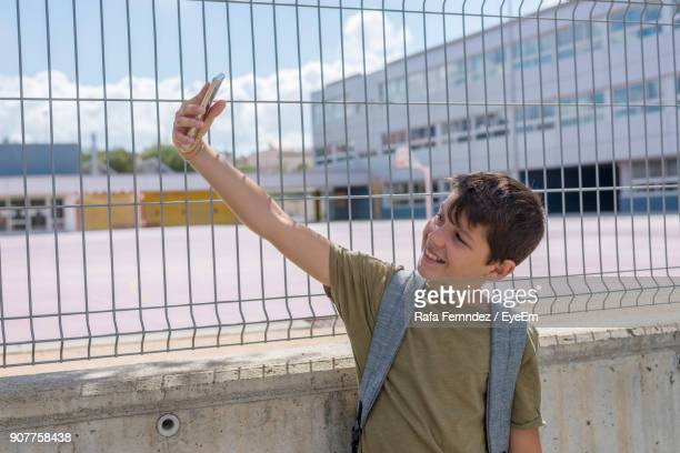 Smiling Boy Taking Selfie Through Mobile Phone While Standing Against Wall