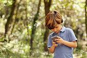 Lachende jongen gebruik mobiele telefoon in bos