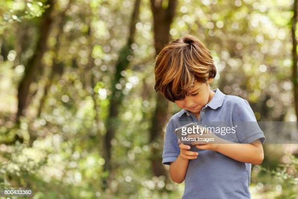 smiling boy using mobile phone in forest - only boys stock pictures, royalty-free photos & images
