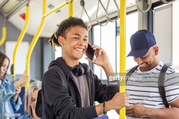 smiling boy using smart phone in bus - izusek stock pictures, royalty-free photos & images