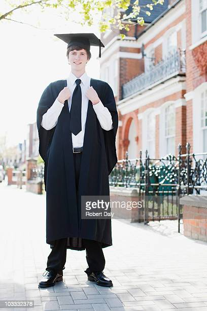 Smiling boy wearing cap and gown on sidewalk