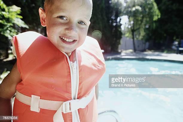 Smiling boy wearing life vest at poolside