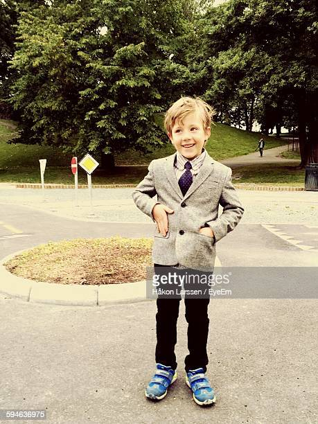 Smiling Boy Wearing Suit With Hands In Pockets While Standing At Park