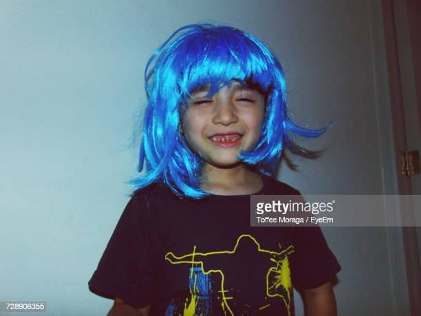smiling boy wearing wig while standing against wall - wig stock pictures, royalty-free photos & images