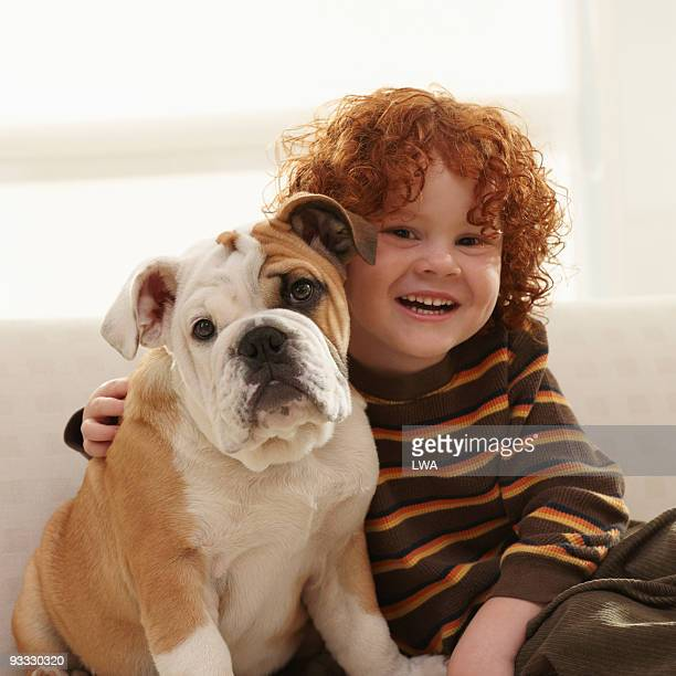 Smiling Boy With Arm Around Bulldog Puppy