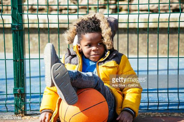Smiling Boy With Basketball Sitting By Fence At Court