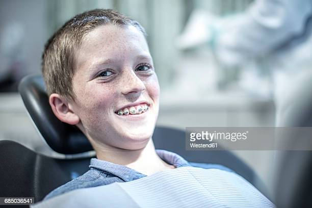 Smiling boy with braces in dental surgery