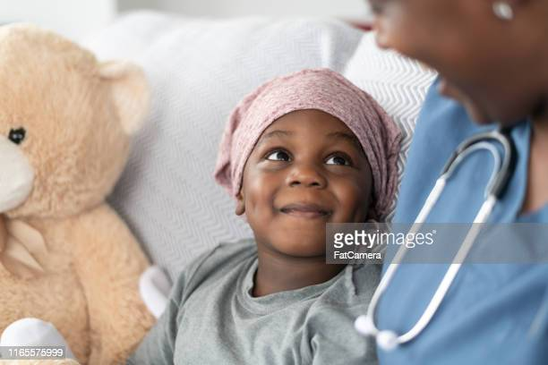 smiling boy with cancer comforted by female doctor of african descent - child hospital stock pictures, royalty-free photos & images